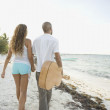 Young couple walking on the beach — Stock Photo