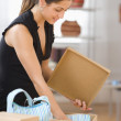 Woman opening box in retail store — Stock Photo #13228868
