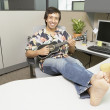 Hispanic businessman dressed casually playing a ukulele at his desk - Stock Photo