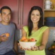 Hispanic couple with bowl of fruit in kitchen — Stock Photo