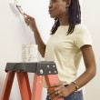 African woman on ladder painting — Stock Photo