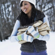 Stock Photo: Asian woman carrying firewood in snow