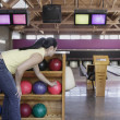 Woman picking bowling ball — Stockfoto