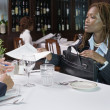 Businesswoman handing papers to man in restaurant — Stock Photo