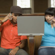 Couple using laptop and mobile phones - Stock Photo