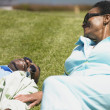 Senior African couple laying in grass smiling — Stock Photo