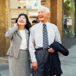 Royalty-Free Stock Photo: Senior couple laughing and walking in urban setting
