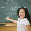Student doing mathematics on the chalkboard - Stock Photo