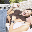 Teenage girls lying in a hammock - Stock Photo