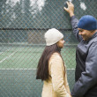 Couple talking by tennis court - Stock Photo