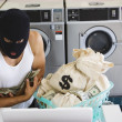 Man in ski mask with bags of money at laundromat — Stock Photo #13229036