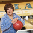 Woman with bowling ball at bowling alley — Stock fotografie