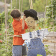 Young Hispanic boy putting hat on scarecrow - Stock Photo