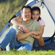 Portrait of father and daughter hugging outside tent — Stock Photo