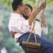 Young Asian couple on swing — Stock Photo