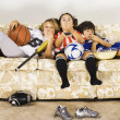 Group of children in sports gear watching television on the sofa - Stock Photo