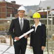 Stock Photo: Businesspeople wearing hard hats at construction site
