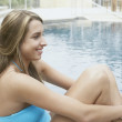 Stock Photo: Young womsitting at poolside