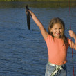 Portrait of girl holding up fish and fishing pole — Stock Photo