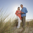 Portrait of couple at beach with wine glasses - Stock Photo