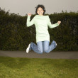 Stock Photo: Young womjumping for joy