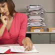 Stock Photo: Businesswomreviewing paperwork at desk