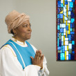 African woman wearing church choir gown and praying - Stock Photo