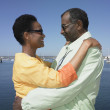 Senior African couple hugging next to water — Stock Photo #13229172