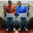 Two men with laptops on couch — Stock Photo #13229191