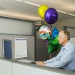 Senior businessman in a cubicle with a bunch of retirement balloons — Stock Photo