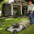 Portrait of elderly man mowing lawn — Stock Photo