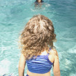 Young girl sitting at edge of swimming pool — Stock Photo