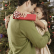 Stock Photo: Hispanic father and daughter hugging on Christmas