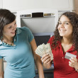 Multi-ethnic teenage girls holding money and credit card — Stock Photo