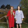 Couple in robes watering yard - Stock Photo