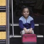 Portrait of girl on school bus steps — Stock Photo