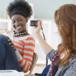 Female college student taking photograph of friend in classroom — Stock Photo