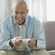 Senior man playing video game — Stock Photo