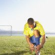 Stock Photo: Soccer player tying shoe