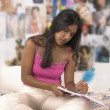 Teenage girl doing homework on bed — Stock Photo