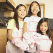 Three young Asian sisters wearing aprons and bunny oven mitts in the kitchen  — Stock Photo
