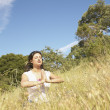 Stock Photo: Wommeditating in field