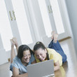Two teenage girls lying on the floor working on a laptop - Stockfoto