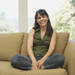 Portrait of woman sitting on couch smiling — Stock Photo