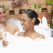 Couple in bubble bath drinking champagne — Stock Photo #13229571