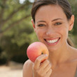 Royalty-Free Stock Photo: Young woman smiling holding apple