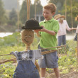 Young boy putting hat on scarecrow — Stock Photo