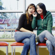 Two teenage girls talking on cell phone — Stock Photo