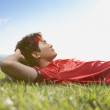 Soccer player lay in grass resting head on ball — ストック写真