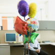 Bunch of retirement balloons in front of a businessman in a cubicle — Stock Photo